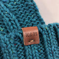 on the raised cuff of the women's teal cable knit beanie is a brown leather kb label