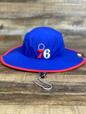 On the front of the Philadelphia 76ers Adventure Panama Bucket Hat is a 1970s retro vintage Sixers logo in red white and blue, and a view of the hot red piping around the structured brim