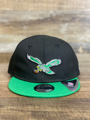 on the front of the Philadelphia Eagles Kids Infant 2-Tone Black and Green My 1st Snapback Hat is a retro vintage Eagle logo