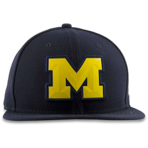 Embroidered on the front of the navy blue snapback hat is the yellow Michigan bevel with navy-blue trim stitch