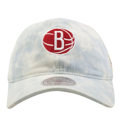 Embroidered on the front of the Brooklyn Nets washed denim usa flag dad hat is the Brooklyn Nets logo embroidered in red and white