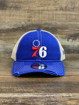 on the front of the Throwback Philadelphia 76ers Distressed Retro Mesh Back Trucker Dad Hat is a vintage 1970s Sixers logo