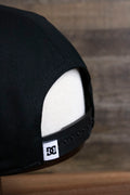 the Black Circle Patch Snapback Skater Hat | DC Shoes Black Bottom Snap Back Cap has a small white DC logo ribbon on ti