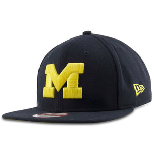 On the front of the Michigan University snapback hat is the Michigan logo in yellow