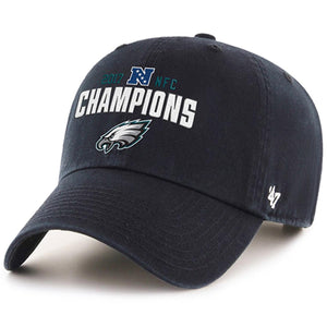 on the front of the philadelphia eagles nfc champions dad hat is the nfc logo embroidered in blue and white above the word champions embroidered in white which is above the philadelphia eagles logo which is embroidered in white, gray, black and pacific green