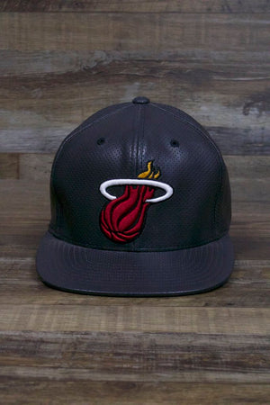 the Miami Heat Perforated Leather Snapback | Black Miami Heat Snap Back with Racing Leather has an extra large Miami Heat logo on the front