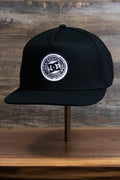 the Black Circle Patch Snapback Skater Hat | DC Shoes Black Bottom Snap Back Cap has a flat brim
