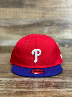 on the front of the Philadelphia Phillies Kids Infant 2-Tone Red and Blue My 1st Snapback Hat is a white current Phils P logo