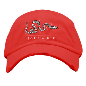 on the front of the red join or die distressed dad hat, the join or die logo is embroidered in white and black