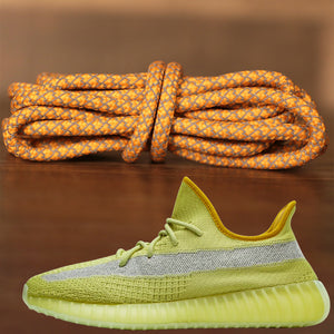 The gold reflective rope Yeezy Matching sneaker laces alongside the Yeezy 350 V2 Marsh sneakers