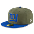on the front of the new york giants 2018 salute to service fitted cap is the new york giants logo in military green and blue