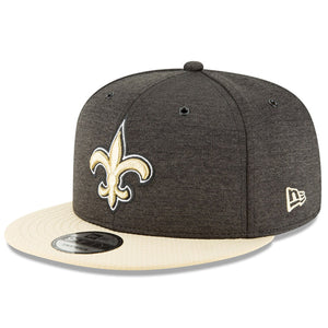 Embroidered on the front of the 2018 New Orleans Saints On Field Sideline Snapback Hat is the New Orleans Saints logo embroidered in tan, white, and black