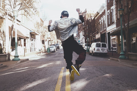A man jumping in the middle of the street.