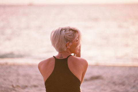 A girl with blonde hair sitting on the beach by the ocean.