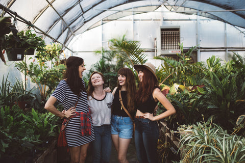 A group of happy women talking around plants.