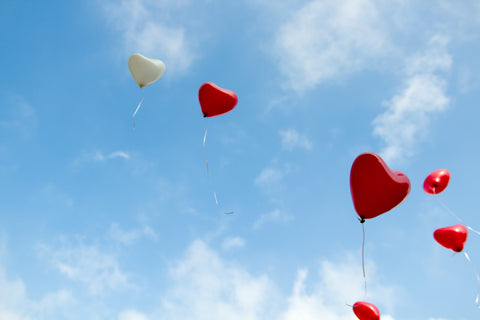 A collelction of red and white heart shaped balloons in the sky.