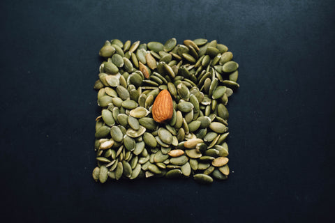 Some pumpkin seeds and an almond.