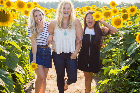 Three happy girls in a sunflower field.