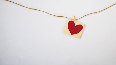A red paper heart on a string.
