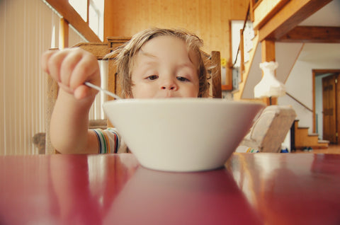A kid eating a bowl of noodles.