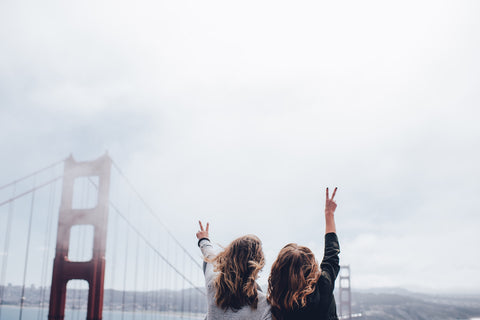 Two girls with their hands in the air by the Golden Gate Bridge.