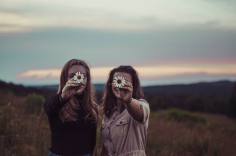 Two girls holding sunflowers.