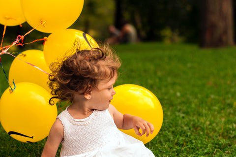 A happy infant with yellow balloons.