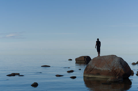 A man by the ocean, standing on a rock.