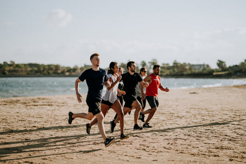 A group of people running on the beach.