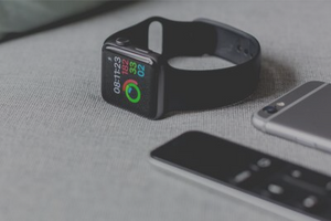 A black Apple Watch lays on the counter top, displaying a fitness tracking app, next to an iPhone
