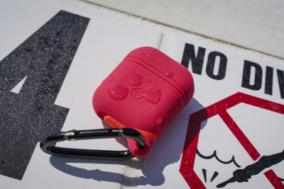A red, water proof, Airpod case cover lays on a in-ground pool sign that says,