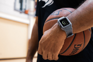 Guy stands on a basketball court wearing a Rhino Brand Apple Watch protector and black T-shirt. He's holding a basketball