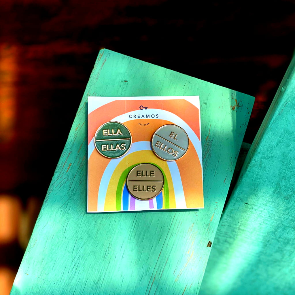 Three enamel pins showing Spanish pronouns mounted on a rainbow colored backer card