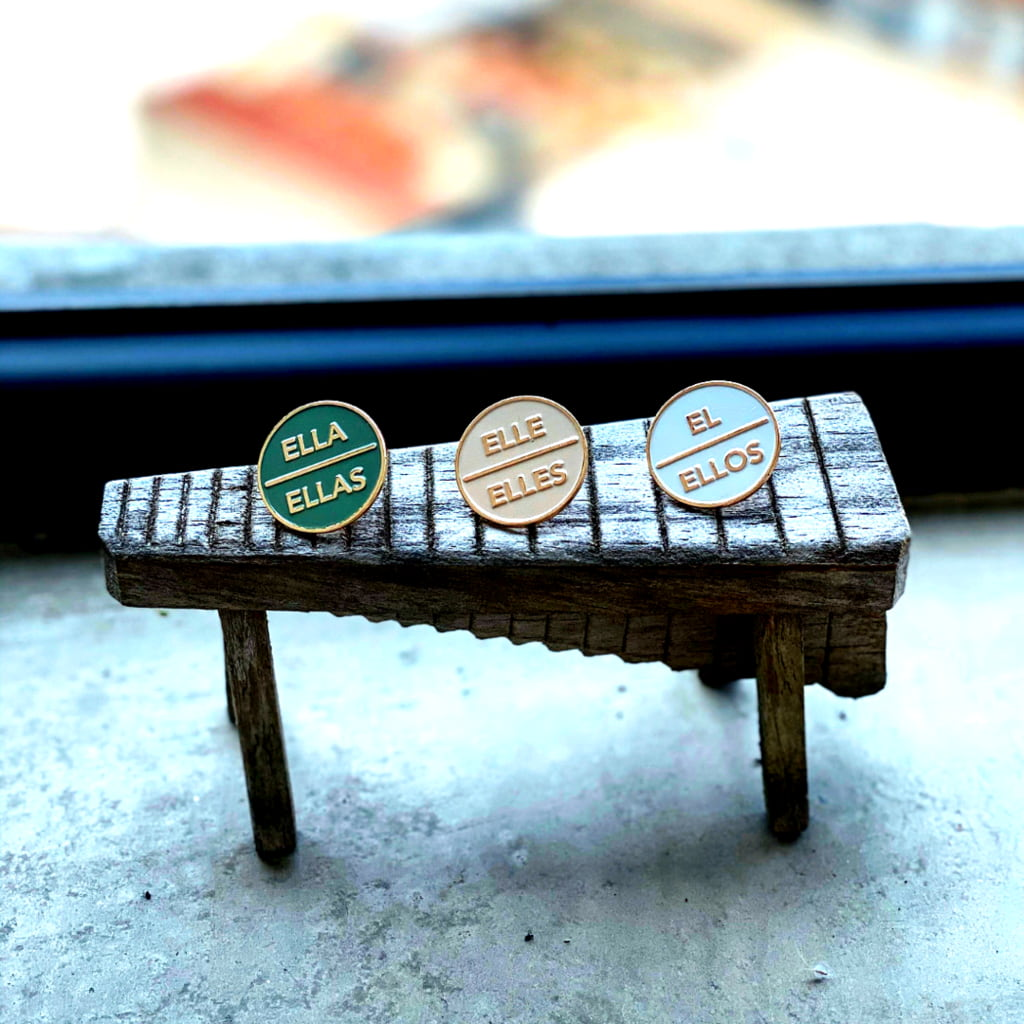 Three enamel pins designed by Cremeos mounted on a stand.