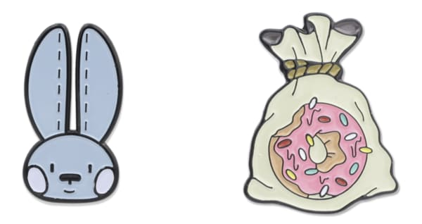 Two enamel pins, one shaped like a rabbit the other a donut in a bag
