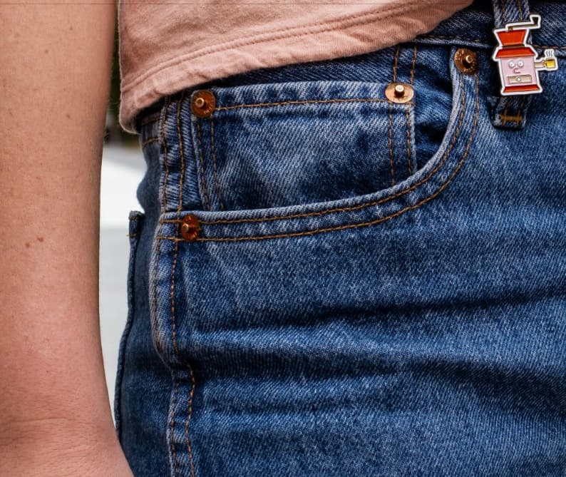 Jeans with an enamel pin attached to the belt loop