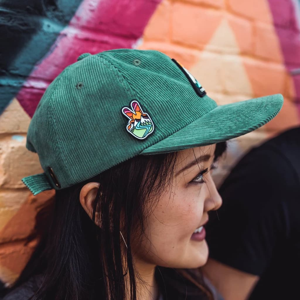 Girl wearing a cap with an enamel pin attached