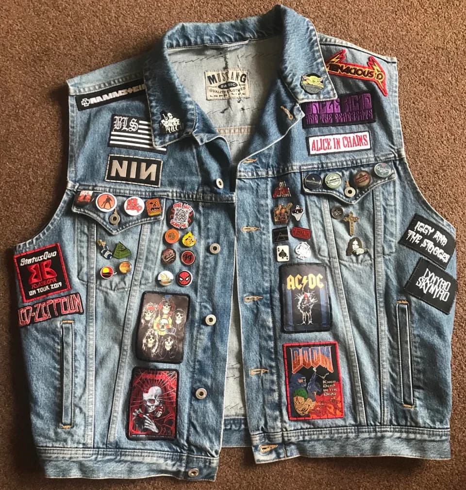 Denim vest filled with patches and enamel pins
