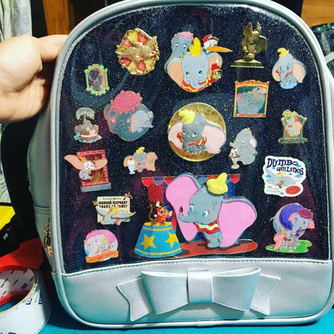 ita bag with several enamel pins attached