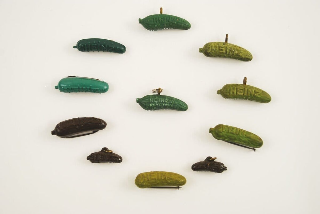 Several Heinz pickle pins and charms