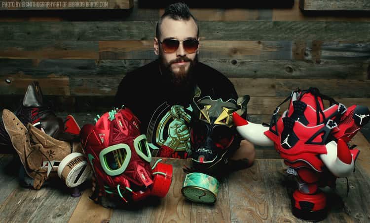 Artist Freehand Profit with several of his mask sculpture