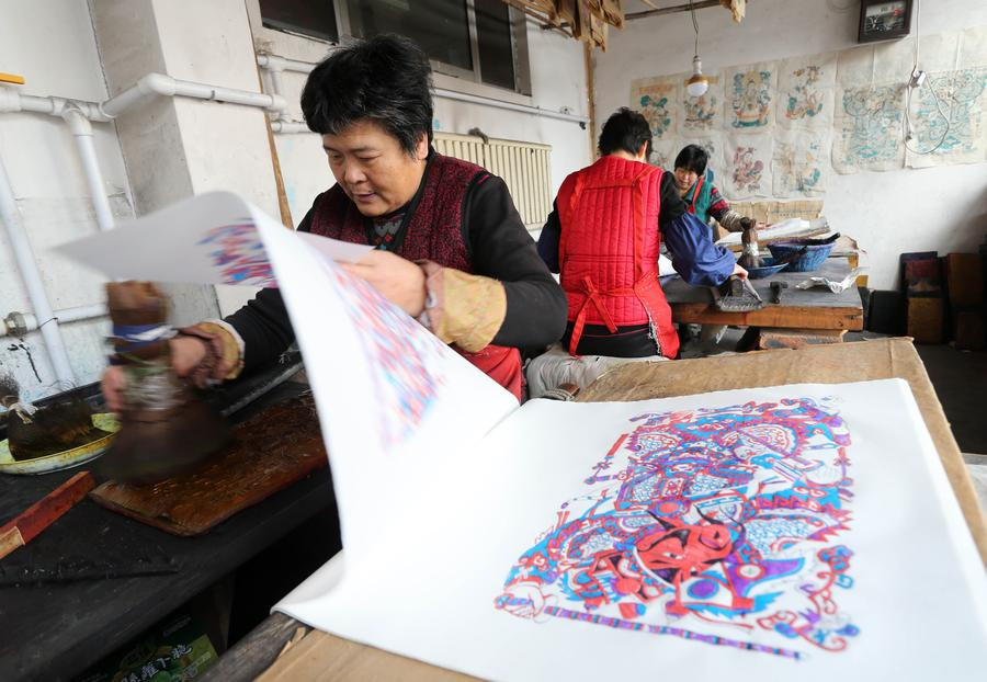 Folk artists hang newly-made woodblock new year paintings up to dry in Yangjiabu village of Hanting district in Weifang, East China's Shandong province, Jan 10, 2017. Local folk artists were busying making woodblock paintings for the Spring Festival market.  [Photo/Xinhua]