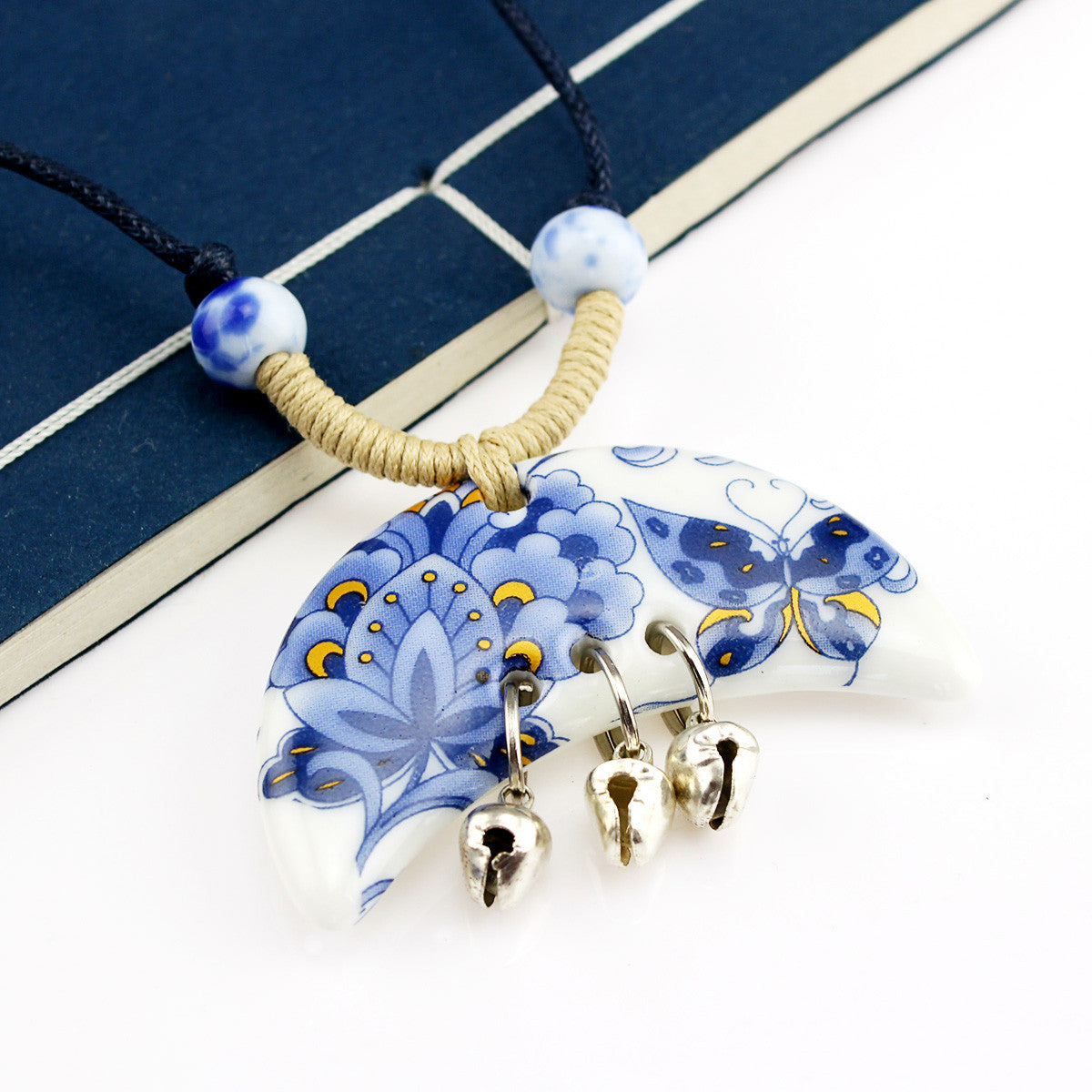 Crescent-shaped blue and white porcelain ceramic necklace with butterfly pendant