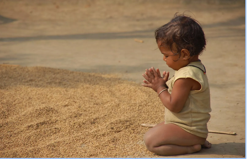 Child praying on the sand