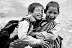 Black and white photo of two school kids hugging