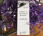 "bookmark with a quote ""Culture is the Luxury of the Mind."" Giesella Perl sitting on the top of confetti"