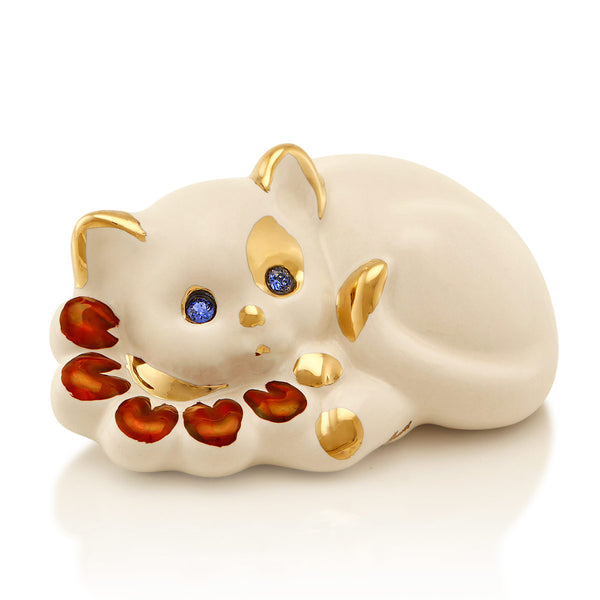 Ceramic little cat lying on flowers