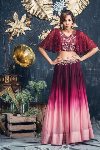 Maroon pinkish ombre rushing lehenga with maroon bat sleeves .