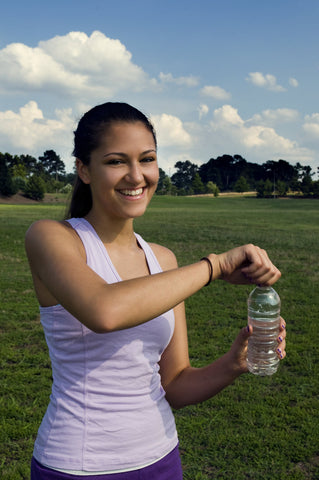 a-young-woman-drinking-bottled-water-outdoors-before-exercising