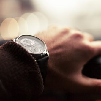 Man-with-watch-on-hand-is-driving-his-car